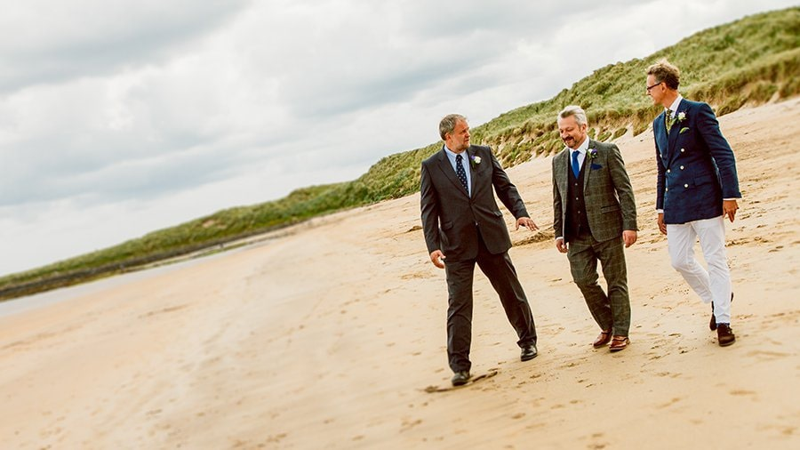 Grooms men walking onto Beadnell Bay in Northumberland