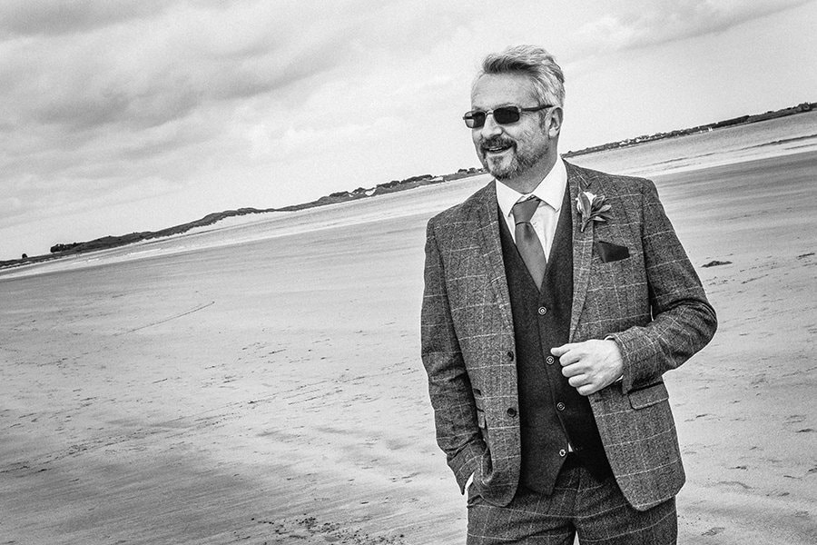The groom posing on Beadnell Bay in Northumberland