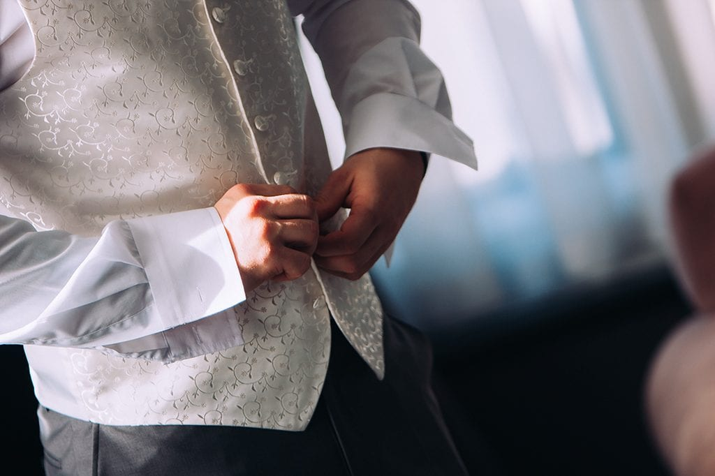 wedding tips groom fastening his waist coat