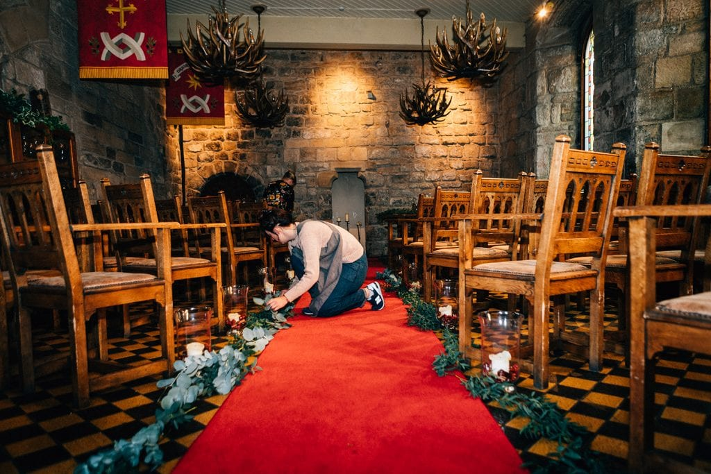 Northumbrian Flowers arranging foliage along the red carpet in Blackfriars Banquet Hall