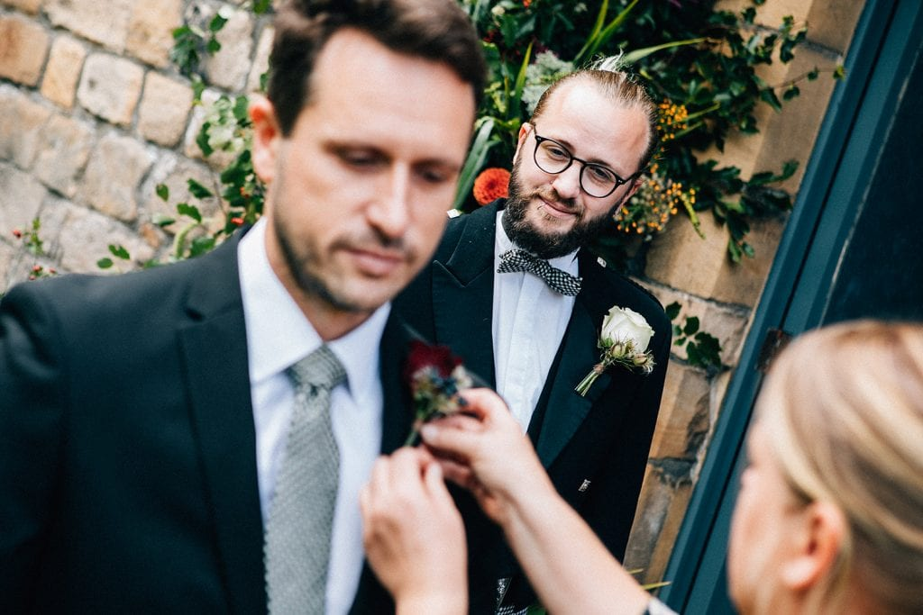 Groom watching Northumbrian Flowers attach the bestmans buttonhole