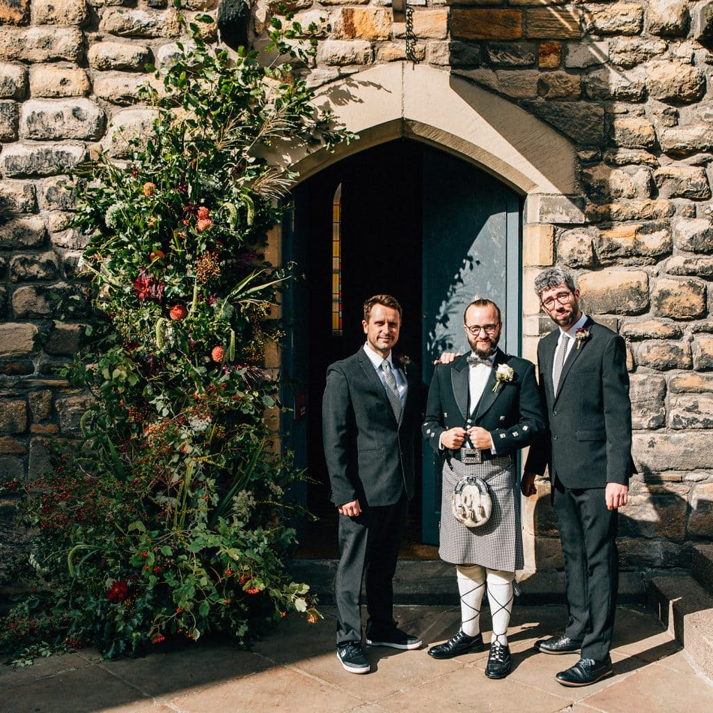 Groomsmen next to a wedding floral arch outside of the banquet hall at Blackfriars in Newcastle.