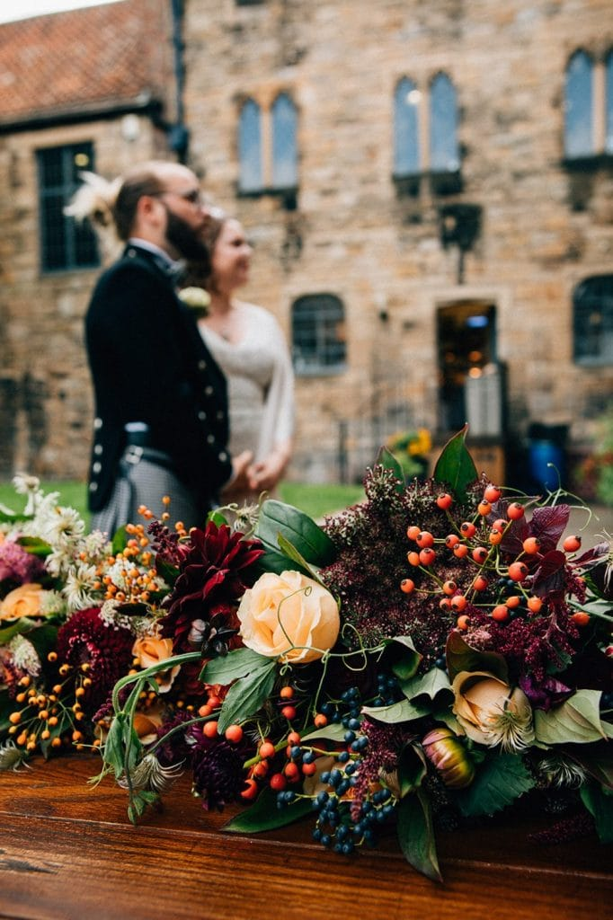 Bride & Groom behind Northumbrian Flowers Bouquets