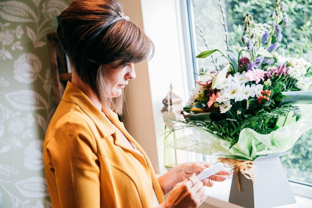 Bride Reading message on flowers sent by groom beforeThe Roker Hotel in Sunderland