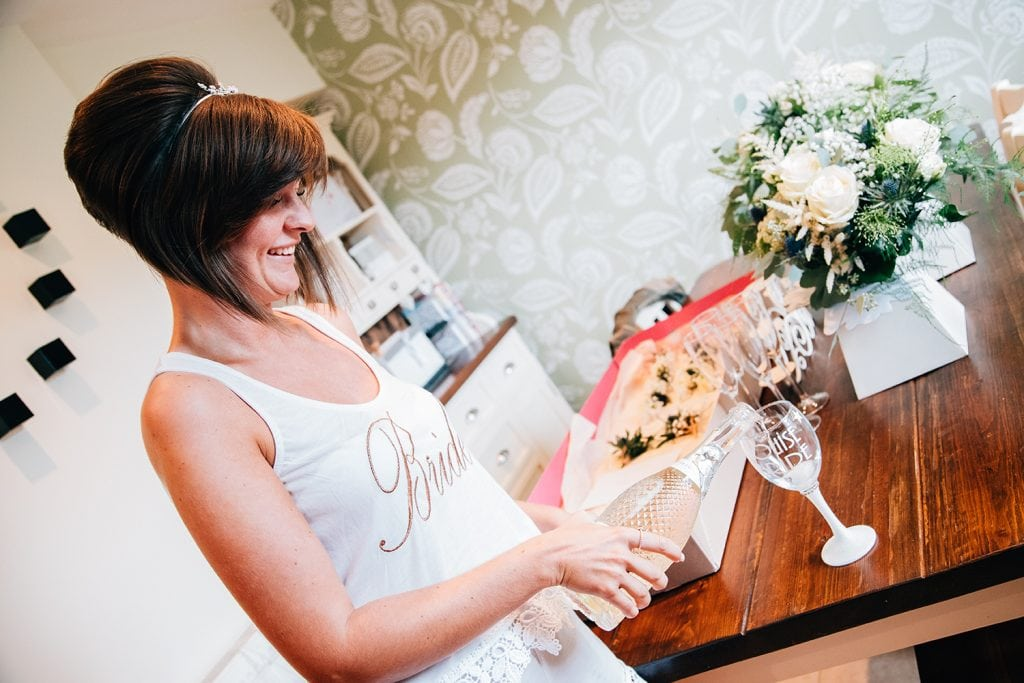 Bride pouring champagne before The Roker Hotel in Sunderland