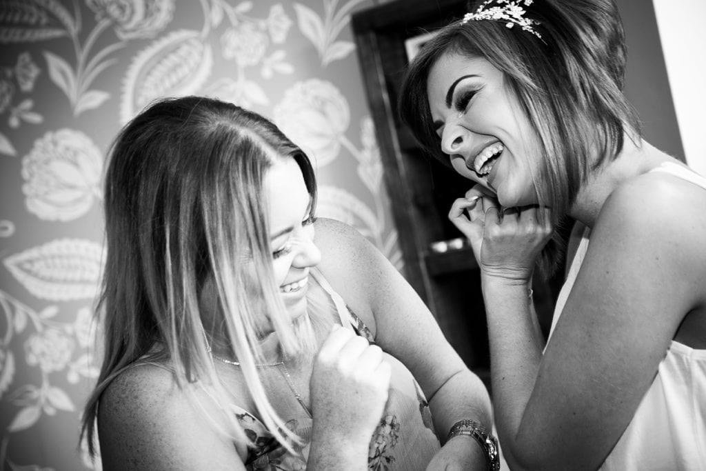 Bride laughing with her sister as they get ready before The Roker Hotel in Sunderland