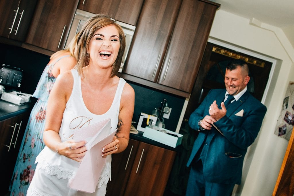 Bride laughing at her Dad before The Roker Hotel in Sunderland