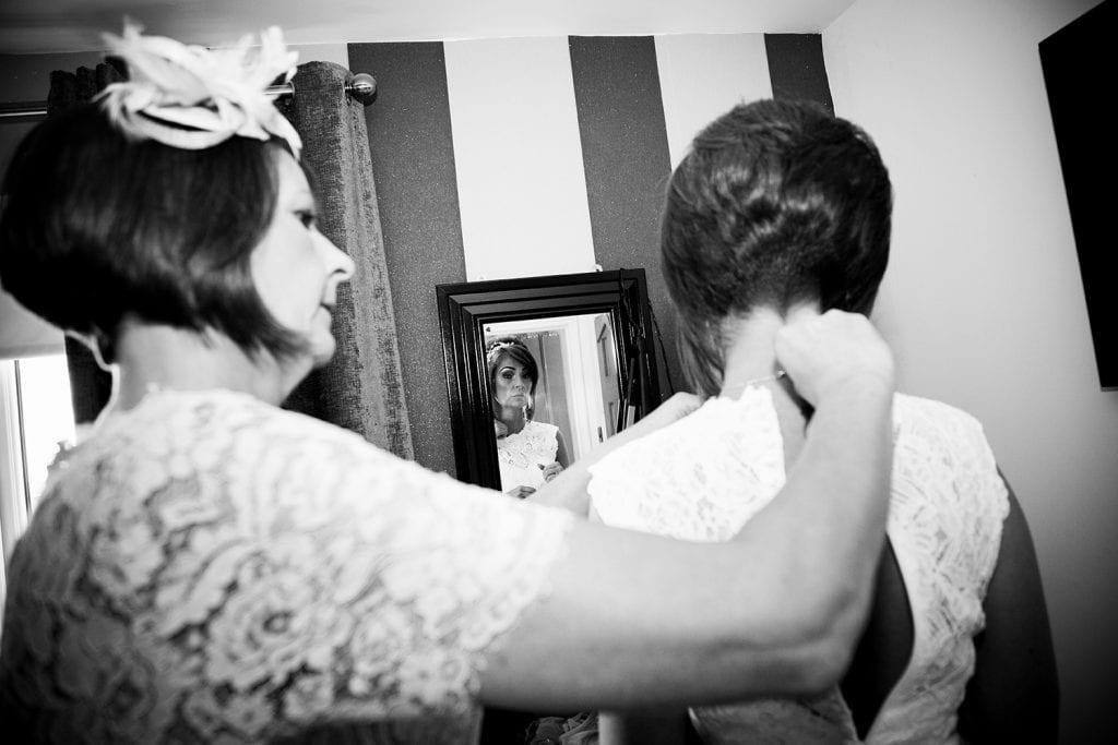 Brides mum helping bride get her dress fastened before The Roker Hotel in Sunderland