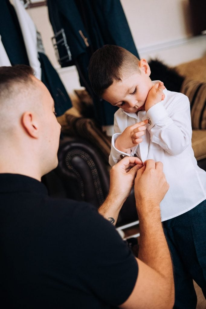 Groom helping his page boy get ready