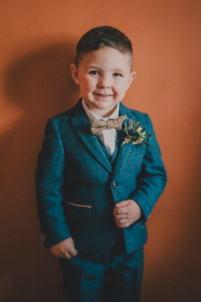 pageboy smiling in his blue tweed suit