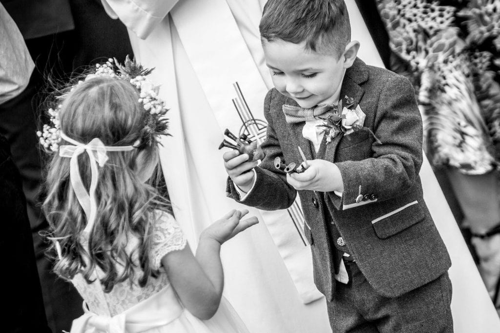 Pageboy showing Flowergirl his toys