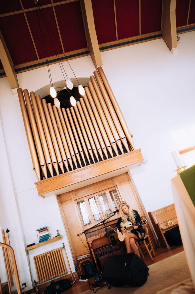 Guitarist next to church organ in St Chad's Church in Sunderland