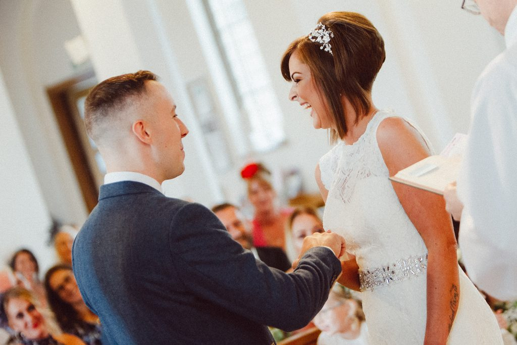 Bride laughing when saying vows in St Chad's Church in Sunderland