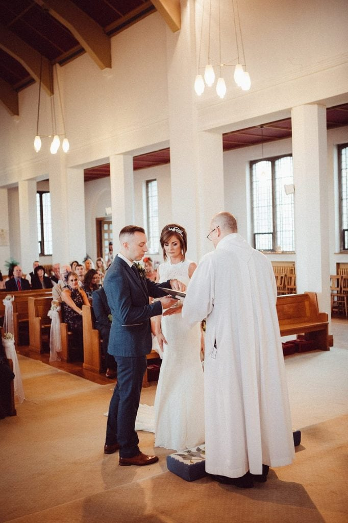 Groom taking the rings from the priest in St Chad's Church in Sunderland