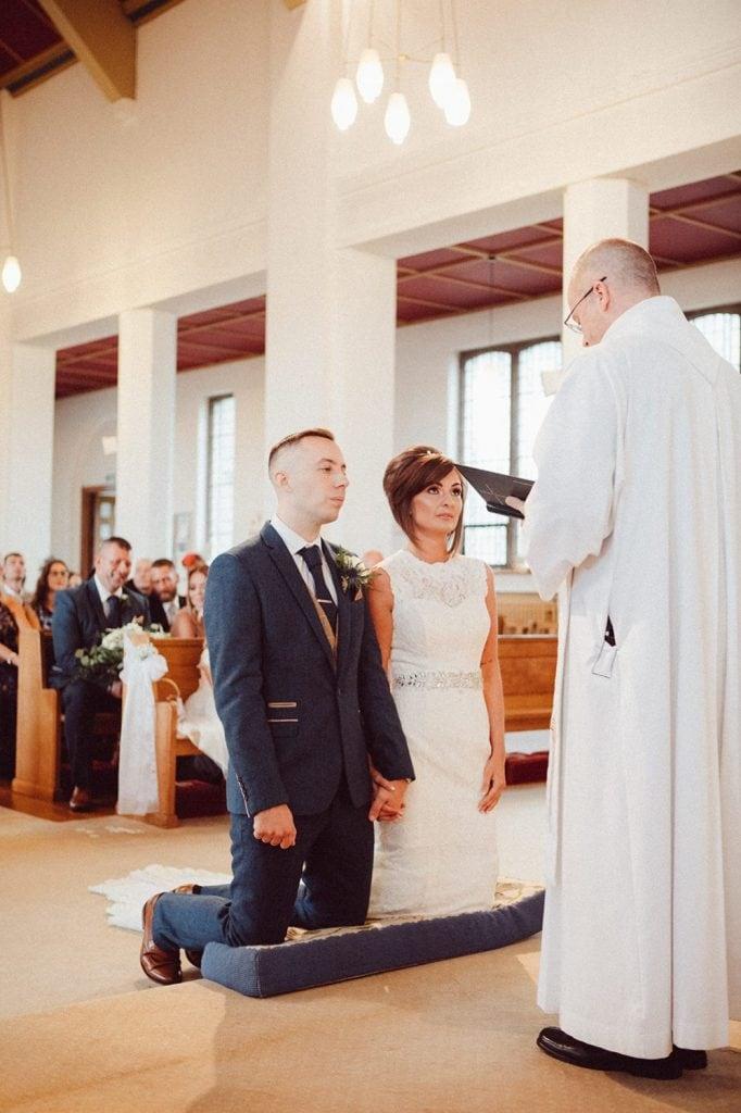 Bride & Groom Kneeing before priest in St Chad's Church in Sunderland
