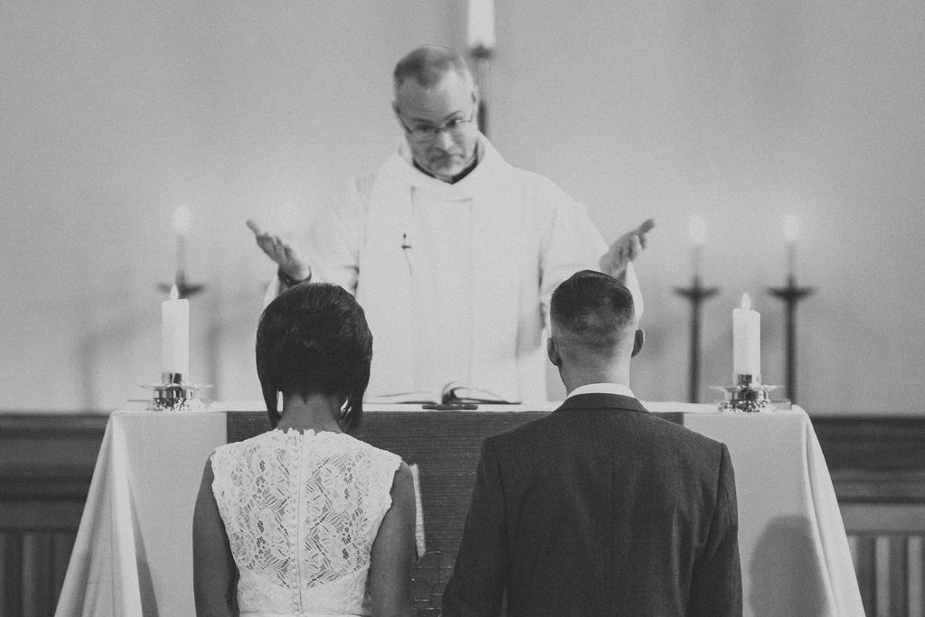 Bride & Groom kneeing before the priest in St Chad's Church in Sunderland