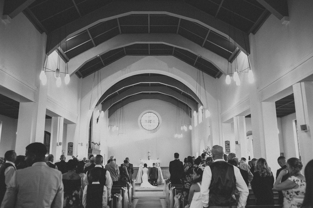Bride & Groom kneeing before the priest viewed from the rear of St Chad's Church in Sunderland