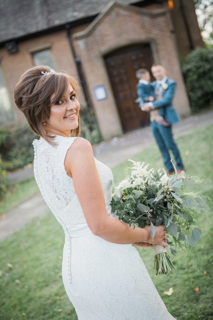 Bride looking over shoulder with groom & son watching in the background outside of St Chad's Church in Sunderland