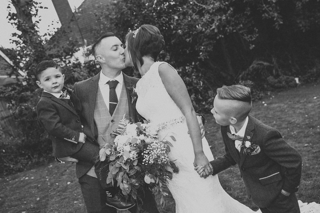 Bride & Groom kissing with sons watching