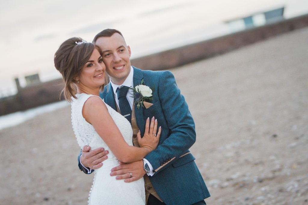 Bride & Groom cuddling on Sunderland Beach Front
