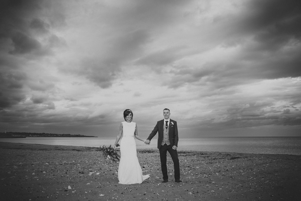 Bride & Groom holding hands in front of dramatic sky on Sunderland Beach Front