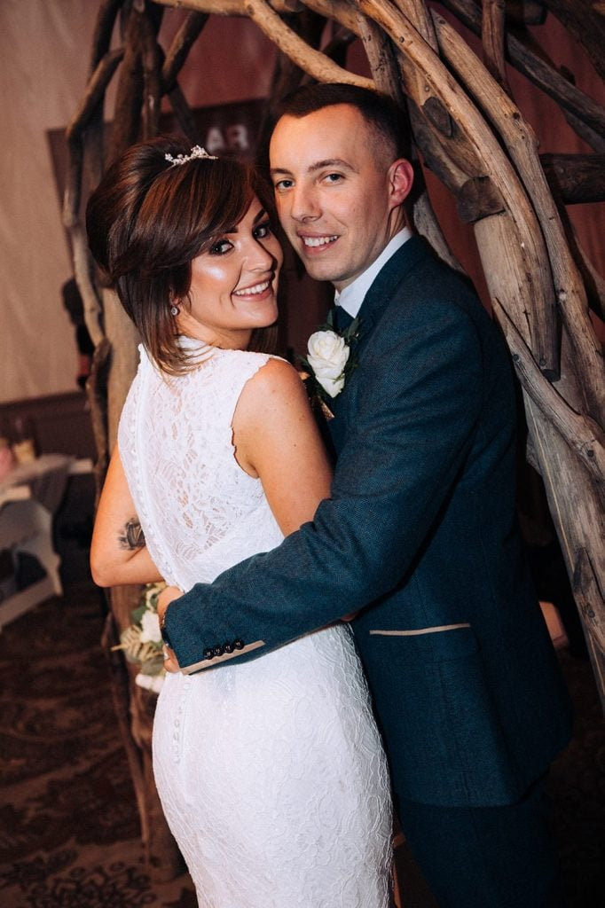 Bride & Groom onder a driftwood arch at The Roker Hotel in Sunderland