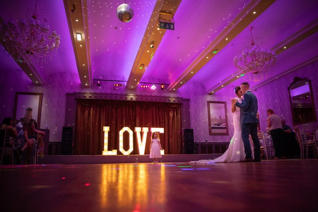 Bride and groom's first dance with flower girl watching at The Roker Hotel in Sunderland
