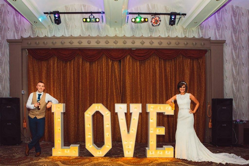 Bride & Groom leaning on letters spelling LOVE at The Roker Hotel in Sunderland