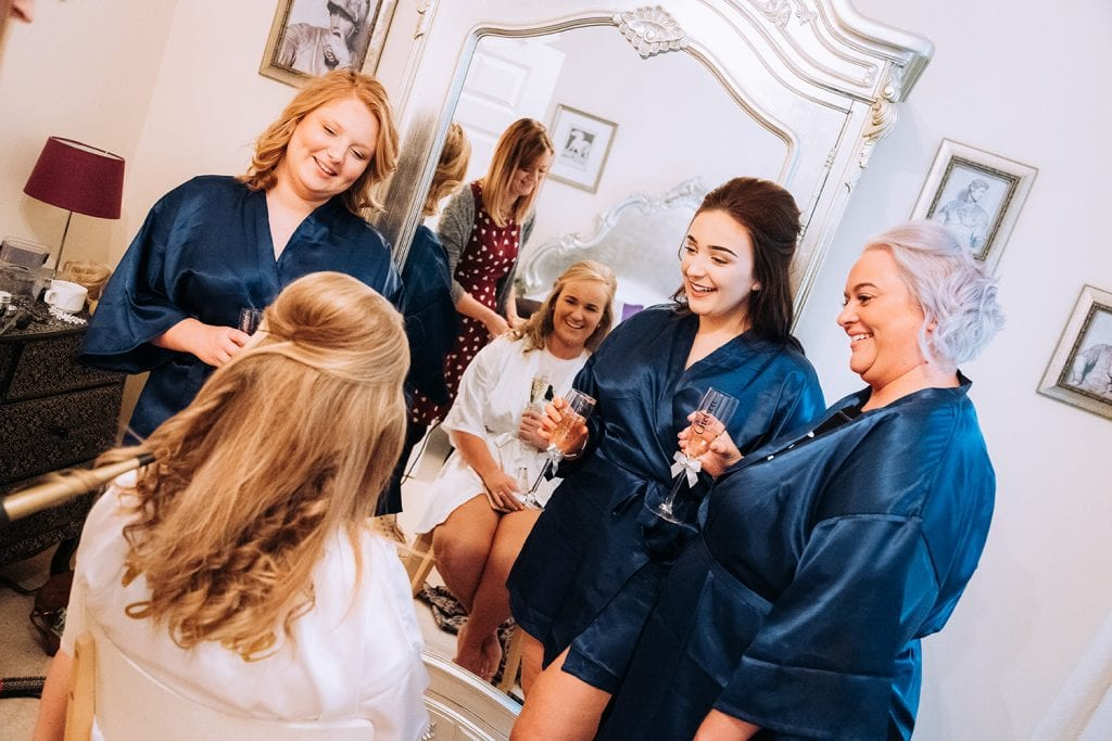 Bride drinking champagne with her bridesmaids