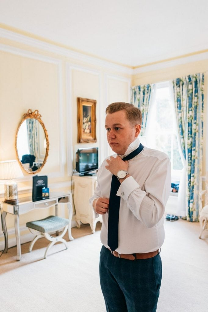 Groom fastening his tie Eshott Hall in Northumberland