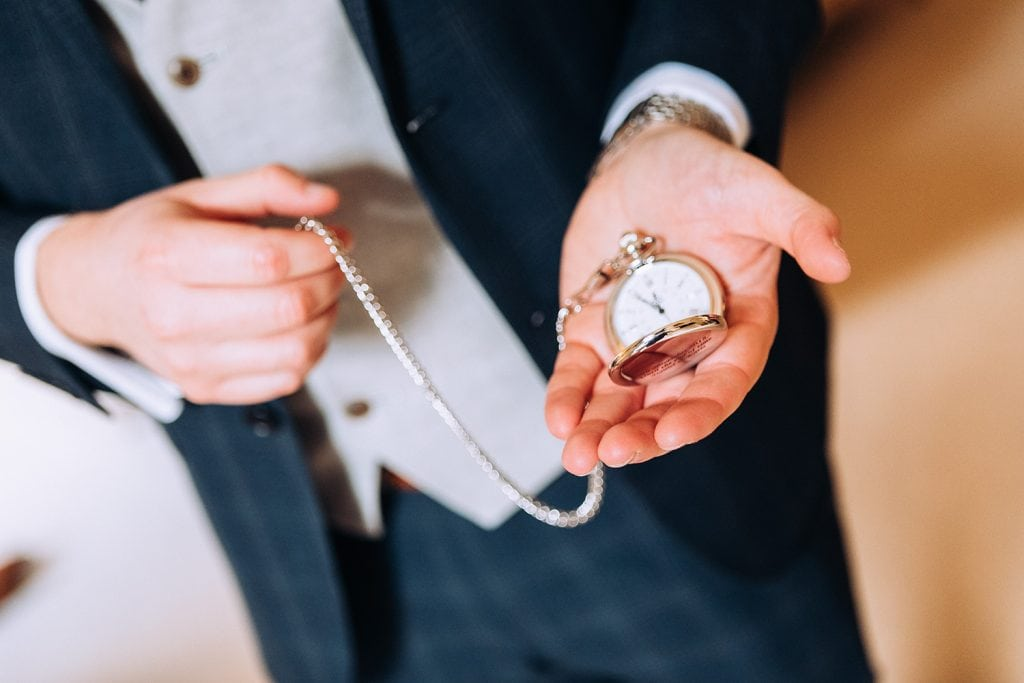 Grooms pocket watch in his hand