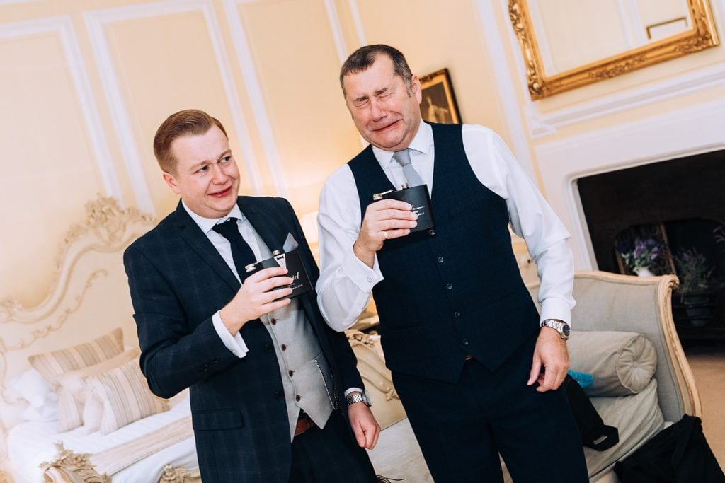 Groom and his dad testing their whisky flasks and pulling faces at Eshott Hall in Northumberland