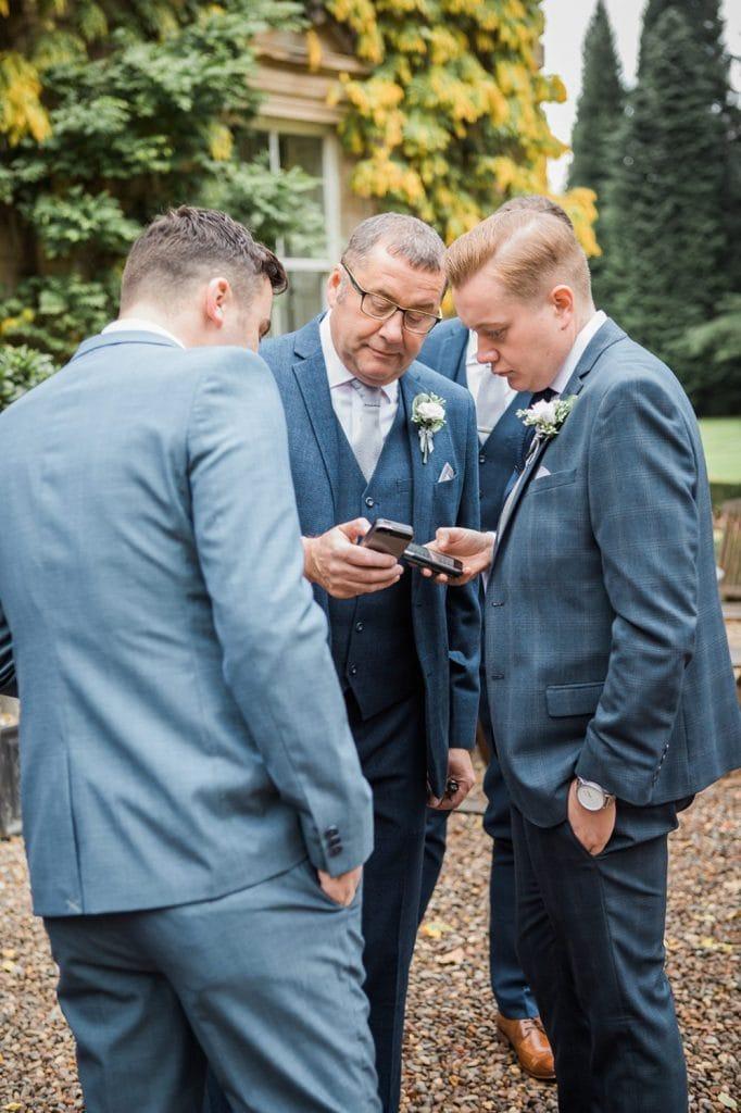 Grooms Men checking their phones Eshott Hall in Northumberland