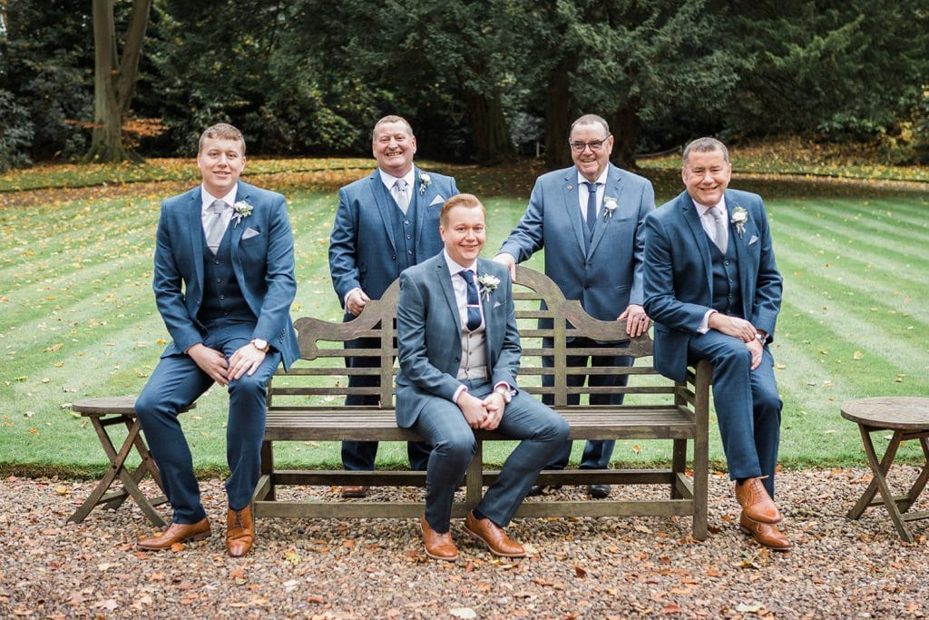 Grooms Men sitting on bench in the Grounds of Eshott Hall in Northumberland