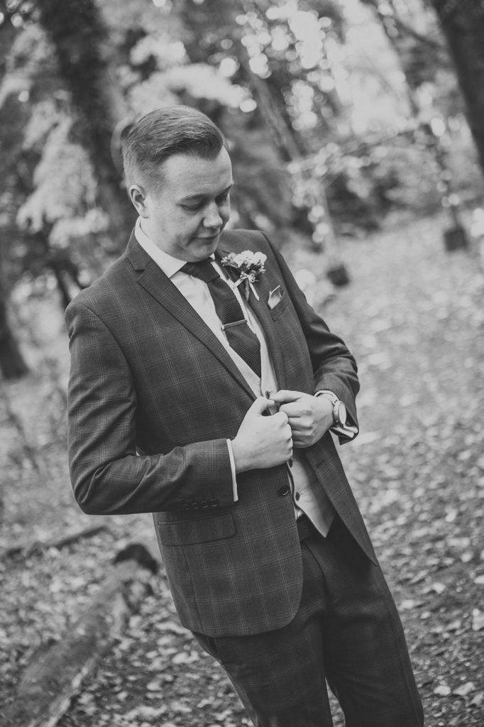 Groom straigtening his jacket in the grounds at Eshott Hall in Northumberland