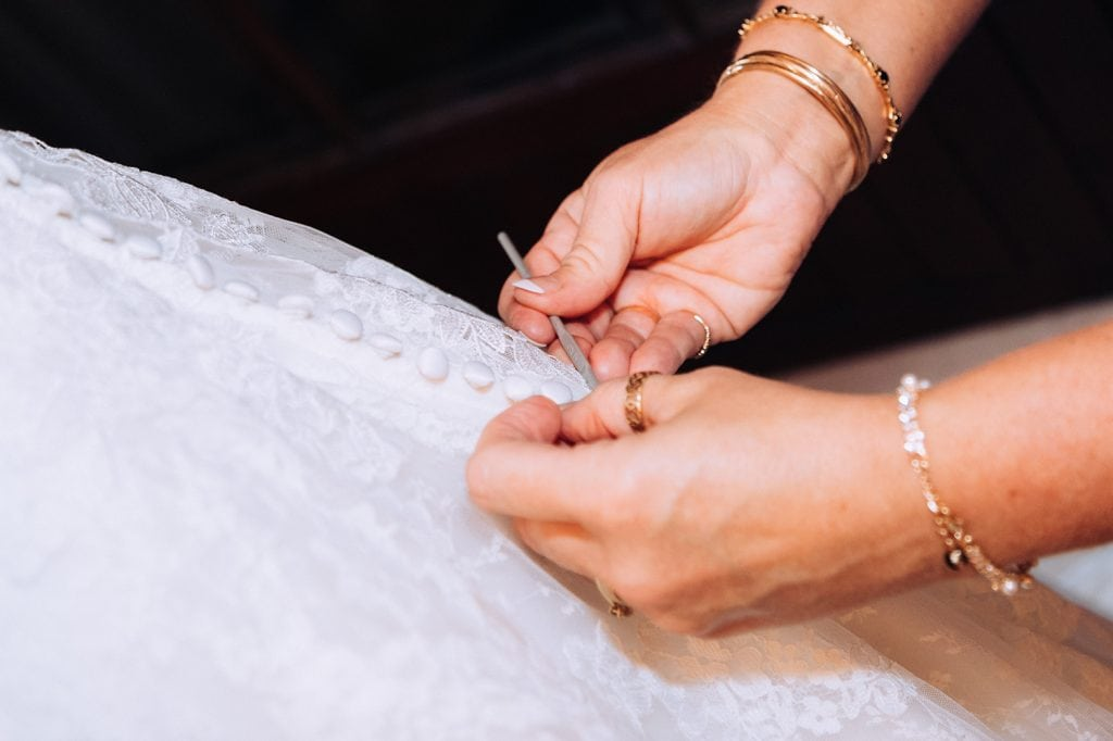 Close up of the Brides mum fastening her dress