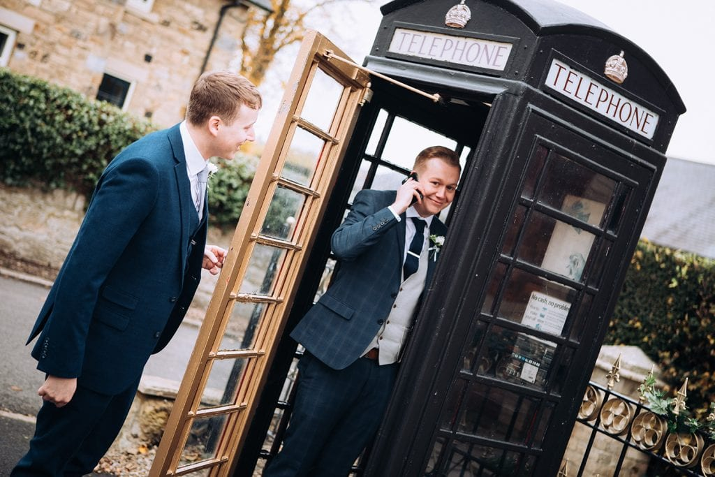 Groom and his brother messing about in the phone box outside the Reading Room in Eshott