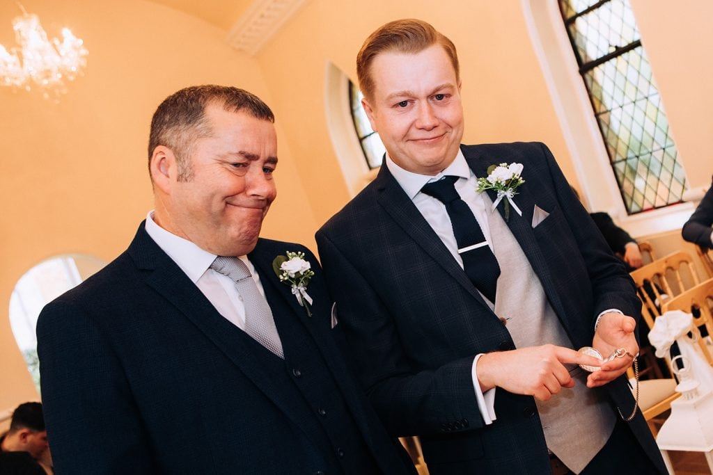 Groom and Bestman looking at their pocket watch and waiting for the Bride at the Groom getting emotional as the bride walks up the aisle at the Reading Room in Eshott