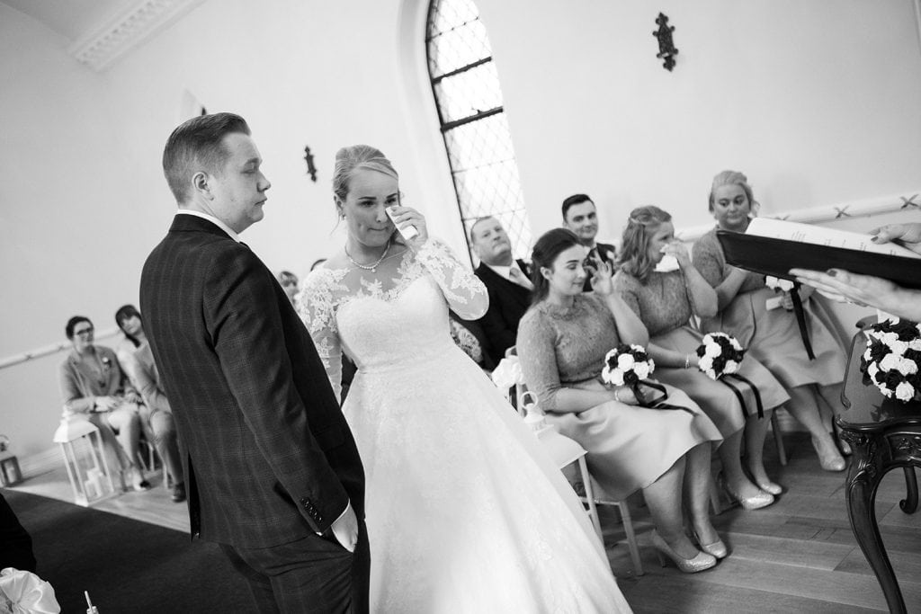 Bride catching a tear during the wedding service at the Reading Room in Eshott