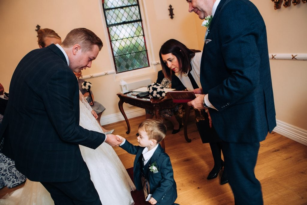 Page boy handing the Groom the weddings ring at the Reading Room in Eshott