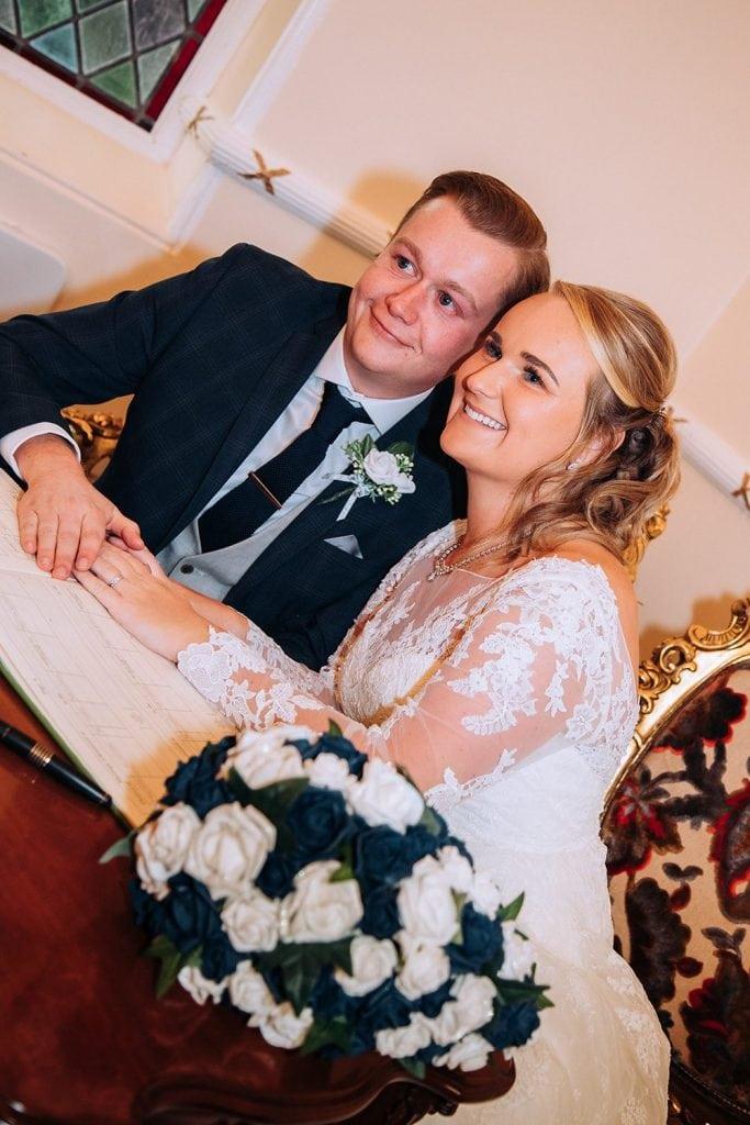 Bride & Groom having their photo taken while signing the wedding register