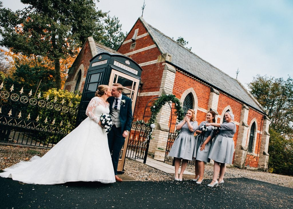 Bridesmaids pointing at the wedding couple in front of the Reading Room in Eshott