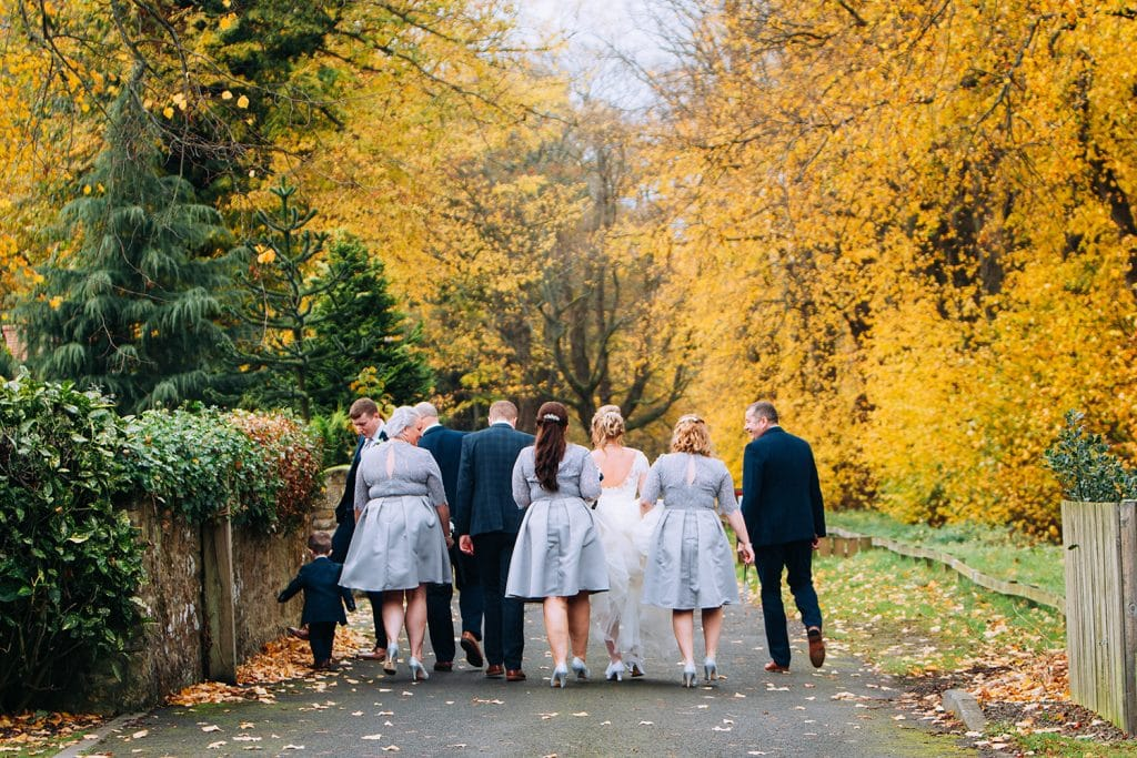 Wedding party walking back from the Reading Room in Eshott