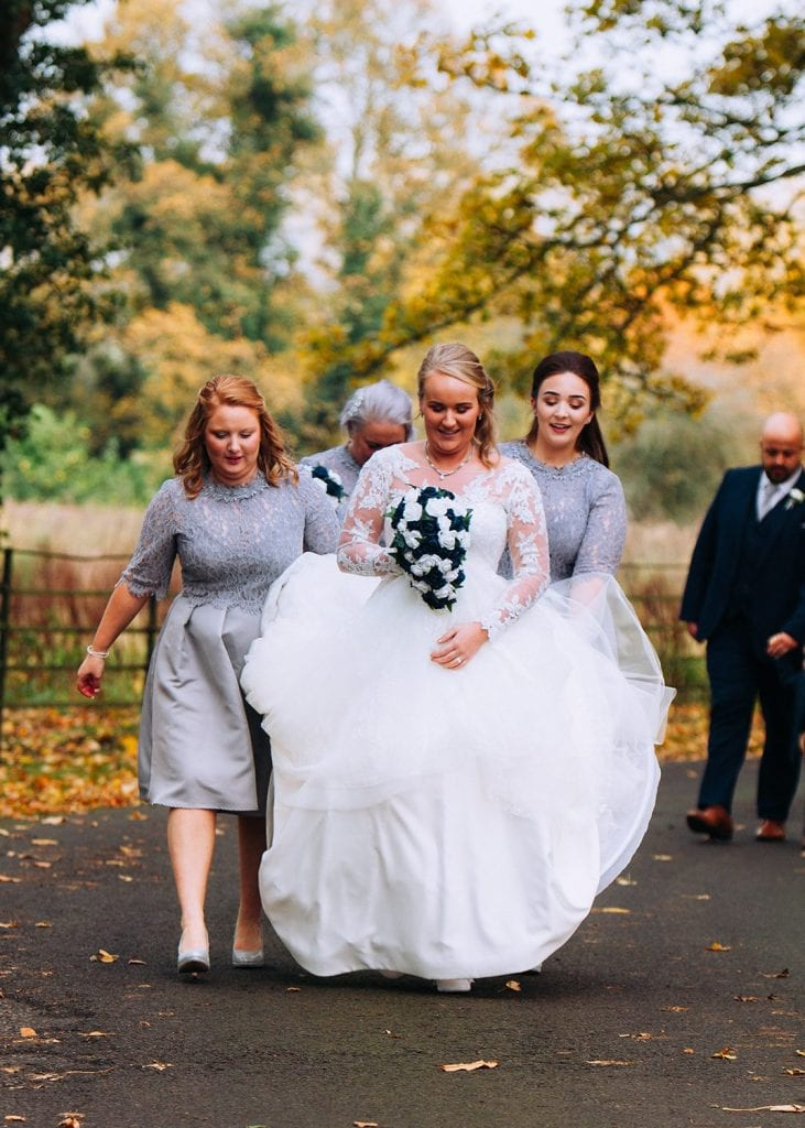 Bride walikng back from the Reading Room in Eshott with brides maids lifting her dress.