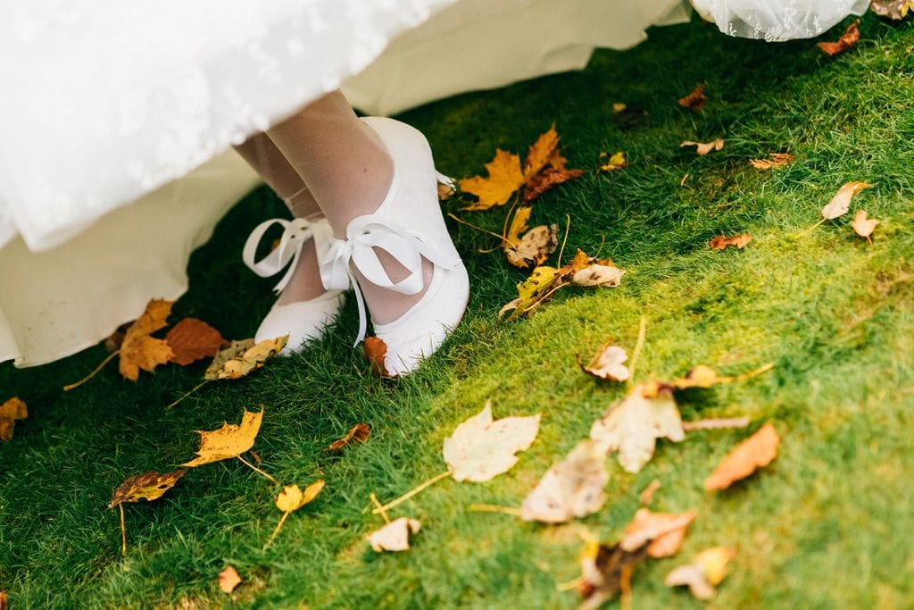 Bride flashing her shoes on the grass with autumn leaves