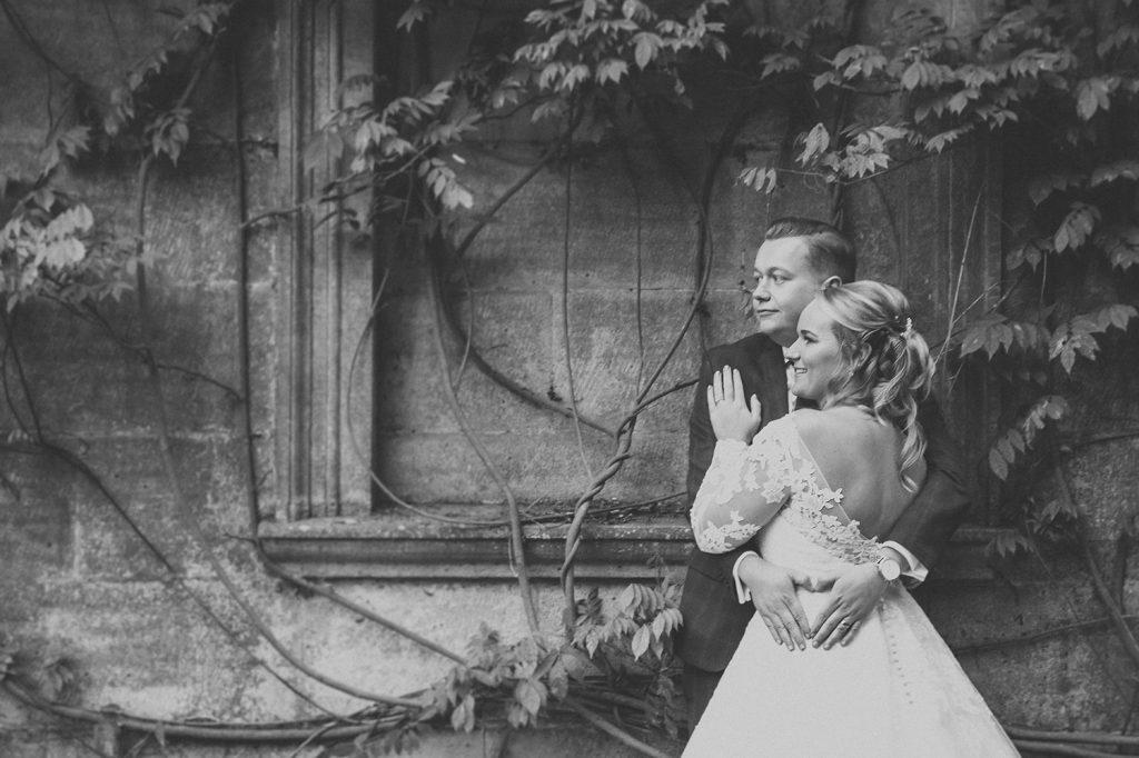 Groom cuddling the Bride against Wisteria Eshott Hall, Northumberland