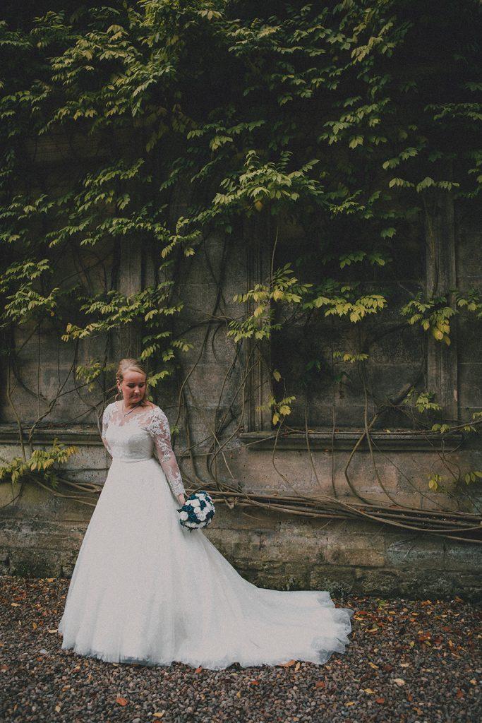 Bride posing against the Wisteria at Eshott Hall, Northumberland