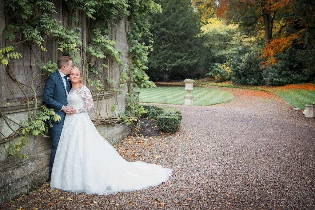 Groom kissing Brides forehead in the grounds of Eshott Hall, Northumberland