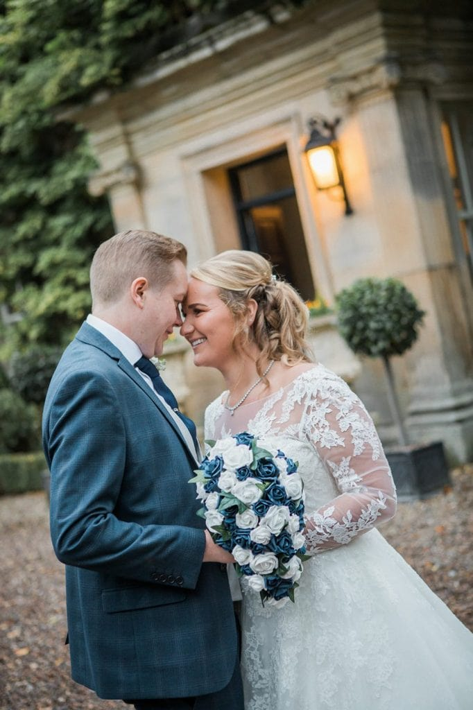 Bride & Groom smiling at each other in front of Eshott Hall enterance