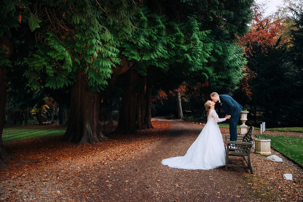 Groom standing on a park bench in the driveway of Eshott Hall, Northumberland